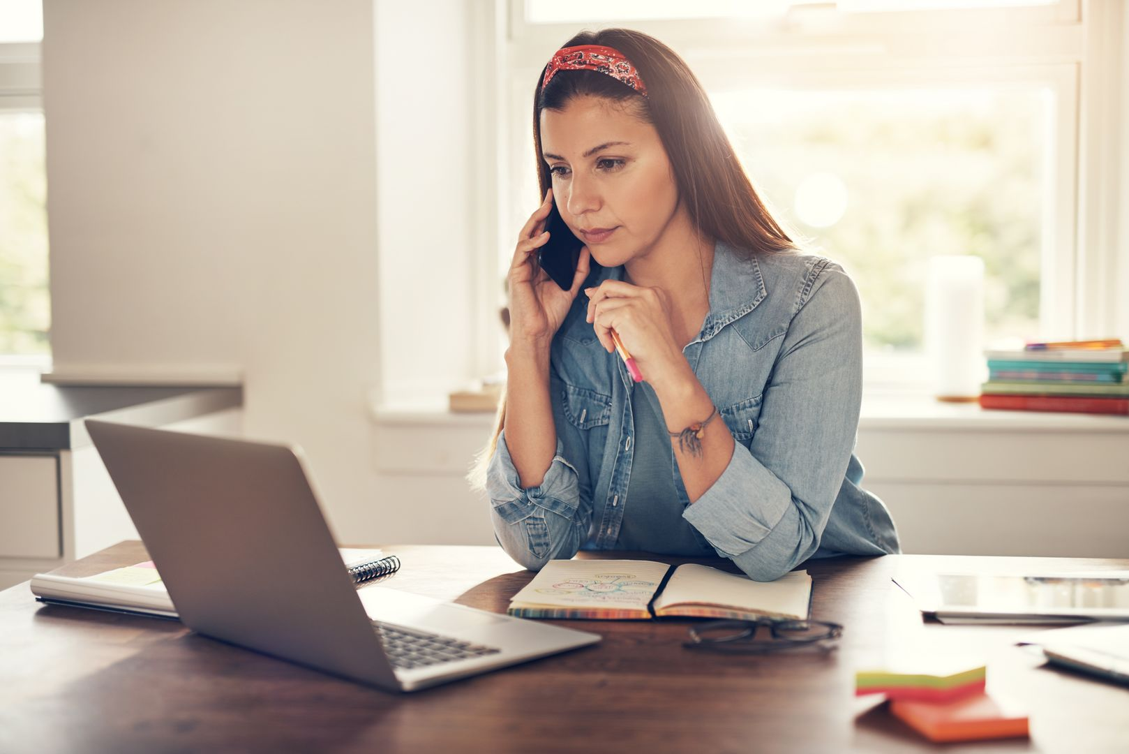 Young female entrepreneur communicating with smartphone while looking at laptop in office.