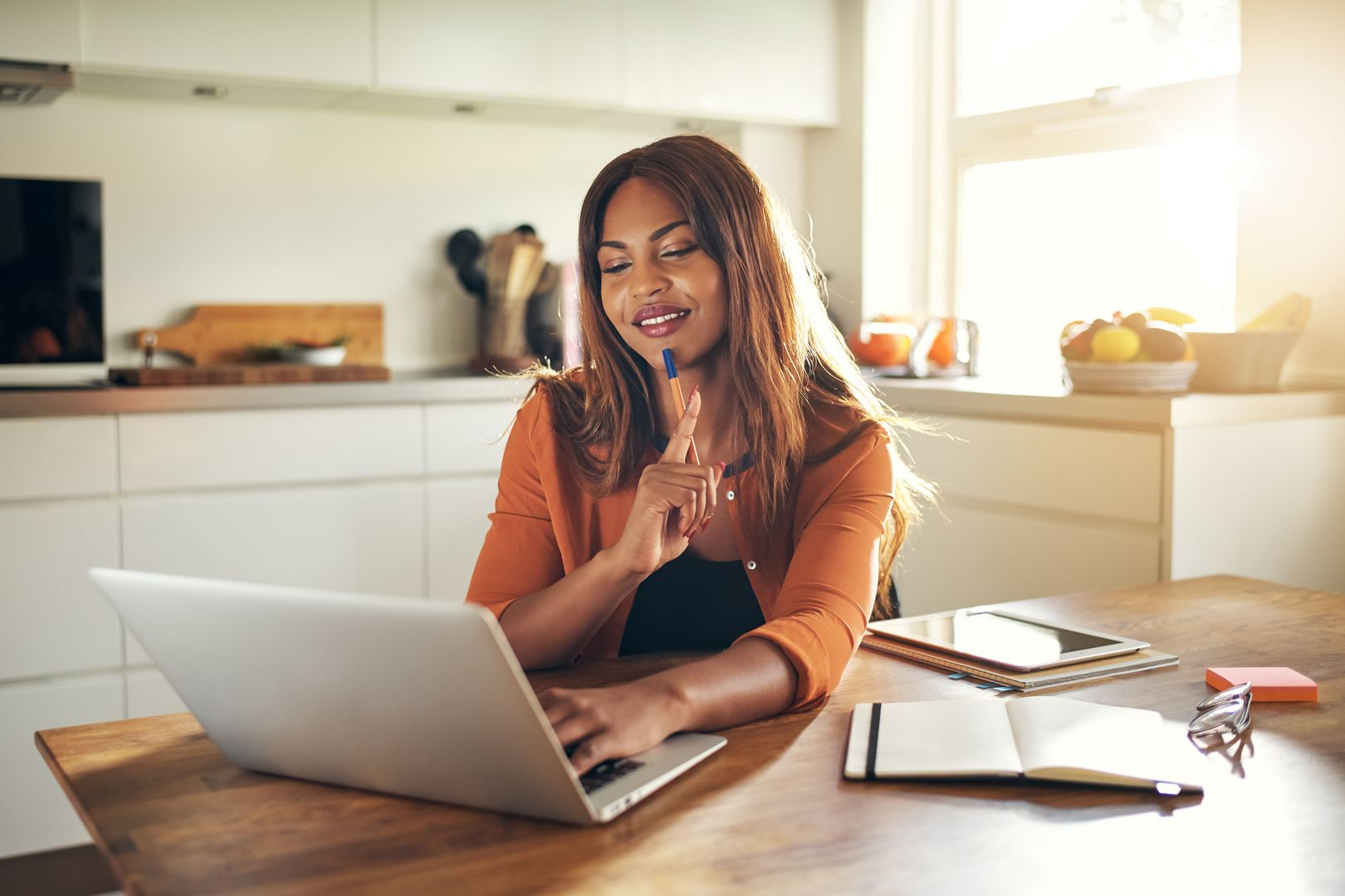 Smiling young African female entrepreneur sitting alone at a table in her kitchen working online with a laptop
